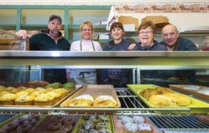 Paul Prebonich, Laura Collins, Allison Collins, Bette Prebonich and Joe Prebonich pose behind a display case at Pep's Bake Shop in Virginia. Photo from Mesabi Daily News.